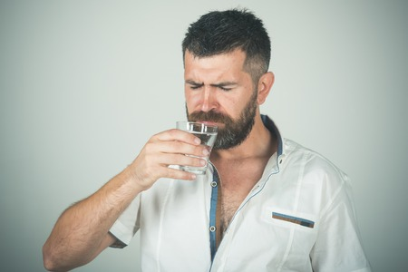 Hipster drink clean healthy water, refreshing. Hangover and thirst. Health and dieting. Life source and healthcare. Man with long beard hold water glass on grey background.
