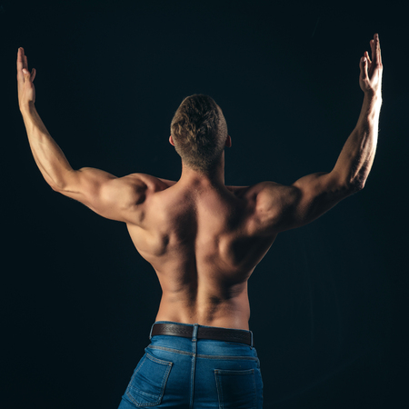 Bodybuilder man show biceps, triceps with raised hands on dark background, back view. Sport, bodybuilding, fitness. Symmetry, muscularity concept.