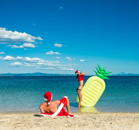 New year girl and guy as santa. Couple in love of happy man and woman in water. Christmas couple with pineapple inflatable mattress. Xmas party celebration and activity. Winter holiday and vacation.
