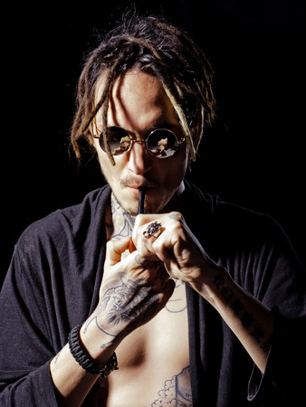 Unhealthy lifestyle concept. Man smoking pipe in tattooed hands on black background. Bad habits, addiction. Hippy smoker with dreadlocks in sunglasses and bare chest. Concentration, stress relief.