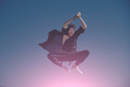 Man samurai jumping with sword on blue sky. Warrior training with katana in sunglasses, black hat and clothes. Martial arts, sport activity. Concentration and zen concept. Defense, power, honor, force