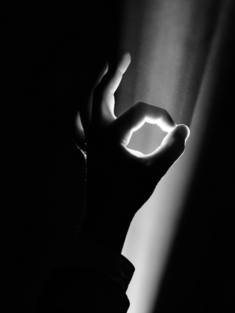 dark silhouette of human male hand with fingers in spotlight or backlight light with okay or ok gesture on black background with dramatic projector shine ray or beam