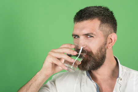 Life source and healthcare. Hangover and thirst. Man smiling with long beard hold water glass on green background. Hipster drink clean healthy water, refreshing. Health and dieting. Imagens