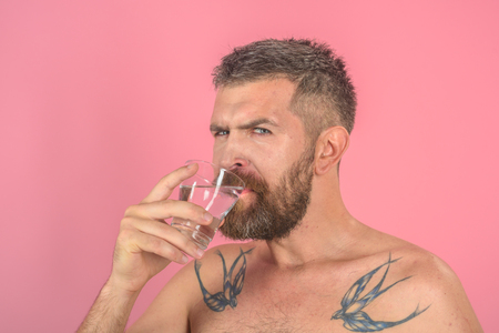 Life source and healthcare. Health and dieting. Man with long beard hold water glass on pink background. Hangover and thirst. Hipster drink clean healthy water, refreshing.