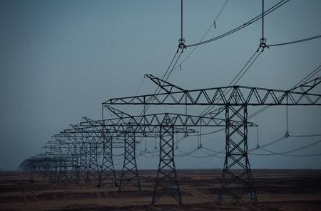 Ecologie, ecovermogen, technologieconcept. Elektrische energieoverdracht. Elektriciteitsdistributiestations. De torens van de machtslijn in woestijn op blauwe hemelachtergrond. Opwarming van de aarde, klimaatverandering.