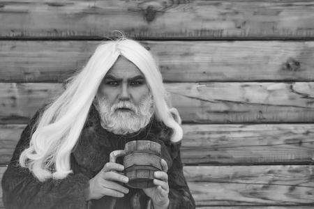 長い灰色の髪と木製のマグカップで真剣な顔にひげを生やしたドルイド老人は、木製の背景に屋外で 写真素材 - 92283606