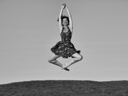 Pretty girl young beautiful woman brunette slim model with bare feet in sexy blue dress jumps on sky background Archivio Fotografico