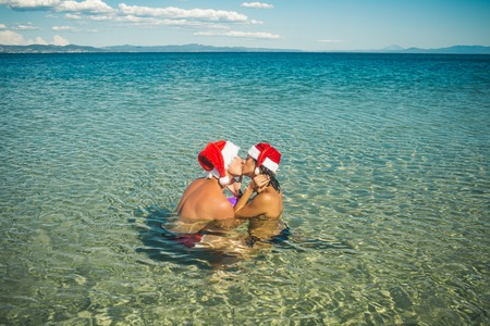 Winter holiday and vacation. Xmas party celebration and activity. Couple in love of happy man and woman in water. New year girl and guy as santa. Christmas couple in red at beach.
