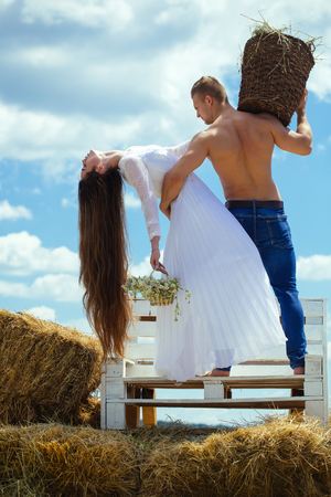 Summer vacation concept. Man with muscular torso hold wicker basket. Woman with long hair in white dress with flowers. Couple in love hug on bench on blue sky. Romance, relationship, relations.