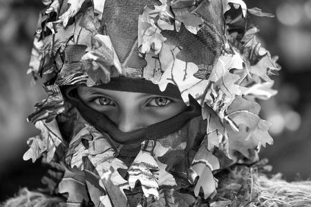 Little girl with blue serious strict eyes in military helmet with net and mask with closed face war camouflage