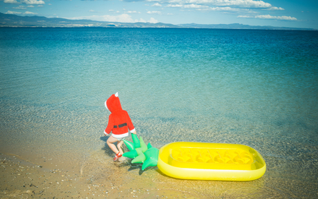 Xmas party celebration, childhood. Christmas happy child with pineapple mattress in water. Winter holiday vacation. Santa claus kid in red Christmas costume. New year small boy at beach.