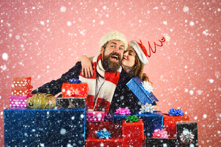 Christmas man and woman couple at present box. Couple in love in santa hat, family relations. Xmas party and love. Winter holiday celebration. New year guy and girl on pink background.