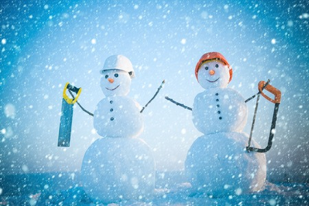 christmas and new year snow concept Christmas or xmas decoration. Happy holiday and celebration. New year snowman from snow with saw. Building and repair work. Snowman builder in winter in helmet.