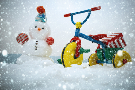 christmas and new year snow concept Snowman and tricycle on snowy background. Snow sculpture in hat on winter day. Bike with present box on white sky. Christmas and new year. Holidays celebration