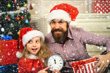 Winter holiday and boxing day. Santa kid, bearded man at Christmas tree. New year small girl, man with clock. Christmas happy child and father with present box. Xmas party celebration, fathers day.