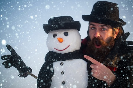 christmas and new year snow concept Man and snowman pointing fingers. Gentlemen in black hats and scarves on blue sky. Surprised hipster with open mouth. Winter holidays celebration. Christmas