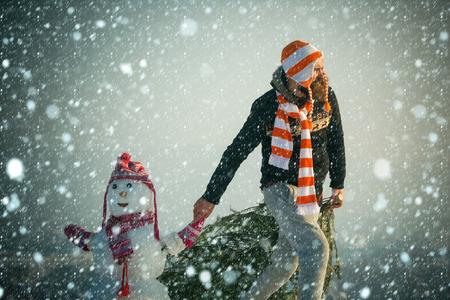 Hipster kerstboom slepen op besneeuwde winterlandschap. Mens en sneeuwman die op blauwe hemel lopen. Vakantie feest concept. Kerstmis en Nieuwjaar. Kerel en sneeuwbeeld die hoeden en sjaals dragen.