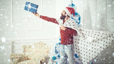 new year christmas snow concept Winter holiday and xmas. Christmas man with beard on serious face hold present box. Santa claus man with toy gift in plaid. New year guy at blue Christmas tree. Boxing