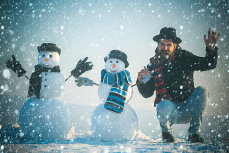 christmas and new year snow concept New year guy gentleman, fashion. Snowman, winter holiday celebration. Christmas man with beard on happy face. Santa claus man with snowman in black hat. xmas