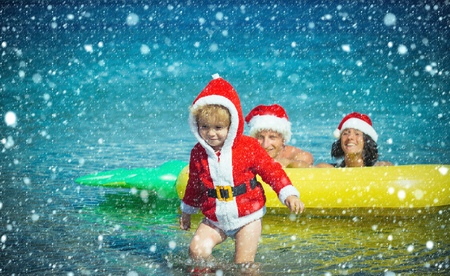 christmas and new year snow concept Winter holiday vacation. Christmas happy family on pineapple mattress in water. Xmas party celebration, fathers and mothers day. Santa child, parents at Christmas.