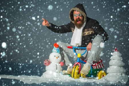 Hipster in pilot glasses and hood pointing finger. Snowman and snow xmas tree on winter landscape. Christmas and new year fun. Holiday celebration concept. Excited man riding tricycle on grey sky.