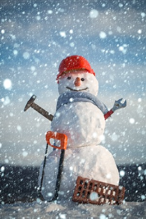 new year christmas snow concept Christmas or xmas decoration. Snowman builder in winter in helmet. New year snowman from snow with saw and brick. Happy holiday and celebration. Building and repair