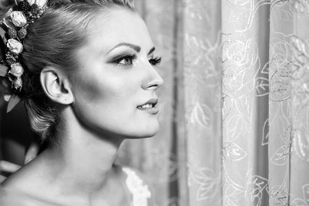 jonge sexy vrouw of meisje bruid met bloemen in stijlvol blond haar en modieuze make-up op mooi gezicht in de buurt van gordijn