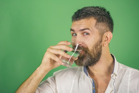 Health and dieting. Hipster drink clean healthy water, refreshing. Hangover and thirst. Life source and healthcare. Man smiling with long beard hold water glass on green background.