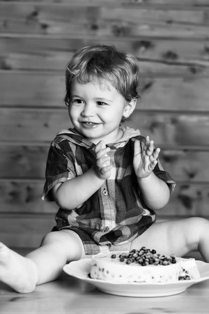 Cute smiling happy baby boy child with blond curly hair eats delicious cake with blueberries sitting on wooden table Stock Photo