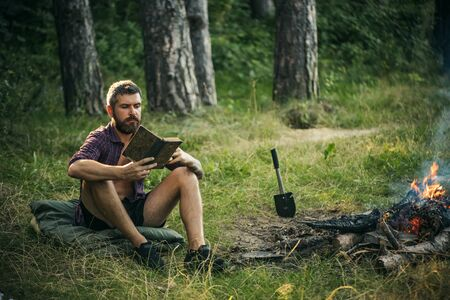 Camping, hiking, lifestyle. Summer vacation, activity. Hipster hiker with book and mug at bonfire in forest. Sustainable education, environment concept. Man traveler read and drink at campfire flame. Stock Photo