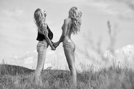 young pretty women with long lush curly blonde hair and sexy bodies standing in green field with grass and blue cloudy sky outdoor on natural background Stock Photo