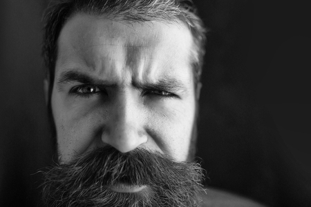 young handsome bearded man portrait with hipster beard and mustache on surprised face on black abckground, copy space