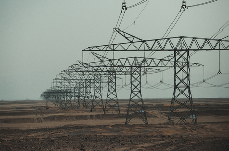 Electric energy transmission. Electricity distribution stations. Global warming, climate change. Ecology, eco power, technology concept. Power line towers in desert on blue sky background.