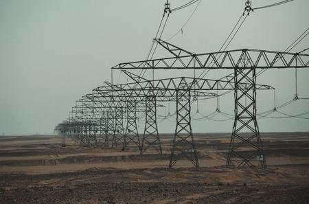 Elektrische energietransmissie. Elektriciteitsdistributiestations. Opwarming van de aarde, klimaatverandering. Ecologie, ecomacht, technologieconcept. De lijntorens van de macht in woestijn op blauwe hemelachtergrond. Stockfoto