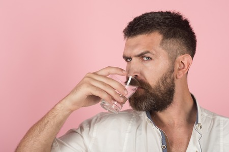 man with beard on face drink water from glass on pink background, healthcare and life source, hangover and thirst, refreshing, copy space
