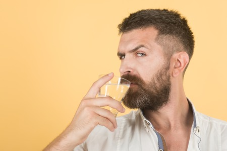 Health and dieting. Hangover and thirst. Life source and healthcare. Man with long beard hold water glass on yellow background. Hipster drink clean healthy water, refreshing, copy space Imagens - 92561549