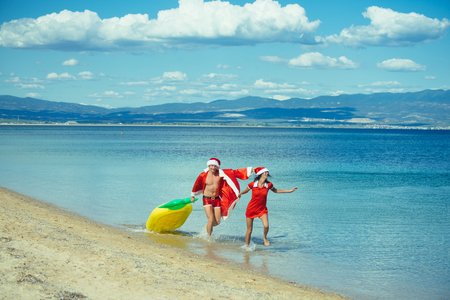 Couple in love of happy man and woman in water. Xmas party celebration and activity. New year girl and guy as santa. Winter holiday and vacation. Christmas couple with pineapple inflatable mattress. Stock Photo