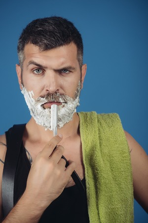 Barber and hairdresser. Man cut beard and mustache with razor and shaving gel. Haircut of bearded man, archaism. Serious hipster in barbershop, new technology. Fashion and beauty, innovation. Foto de archivo