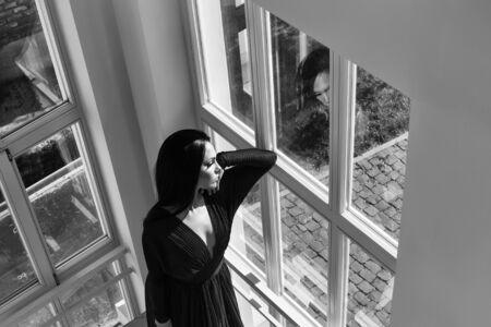창문 근처 우아한 빨간 드레스에 갈색 머리 머리를 가진 젊은 아름다운 여자