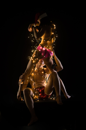 New year boyfriend and girlfriend isolated on black. Relations of couple in illuminated garland. Santa man and girl with naked body. Love and sex games. Christmas couple in love of sexy man and woman. Stock Photo