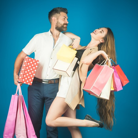 Black Friday, happy holiday, relations. Fashion shopaholic couple. Couple in love hold shopping bag near blue wall. Girl and bearded man hold present pack, cyber Monday. Shopping and sale.