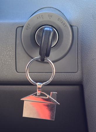 イグニッションの車のキー。エンジンの始動、停止、加速。車両ダッシュボードの背景にハウスシェイプキーフォブ。不動産のコンセプト。