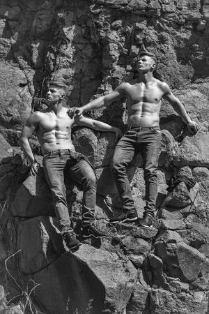 男性裸の若いポーズ双子の兄弟のセクシーなモデルは、壁画の背景に屋外ジーンズで 写真素材