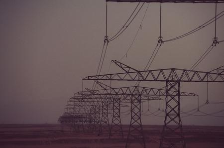 Opwarming van de aarde, klimaatverandering. De lijntorens van de macht in woestijn op de achtergrond van de schemerhemel. Elektrische energietransmissie. Elektriciteitsdistributiestations. Ecologie, ecomacht, technologieconcept.