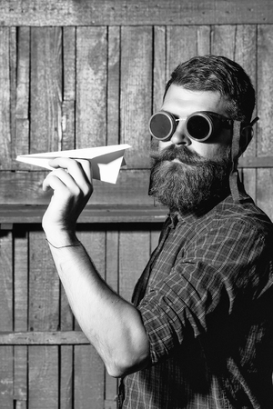 Bearded man hipster brutal male with beard and moustache in vintage biker or pilot sunglasses throws paper plane on wooden background