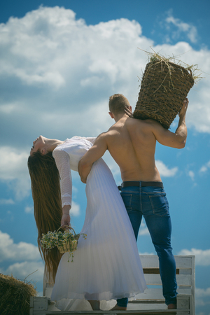 Romance, relationship, relations. Couple in love hug on bench on blue sky. Woman with long hair in white dress with flowers. Man with muscular torso hold wicker basket. Summer vacation concept. Stock Photo