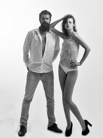 couple of handsome bearded man with long beard on serious face near young pretty girl with sexy body in lingerie in studio isolated on white background Stock Photo
