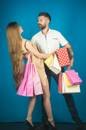 Black Friday, happy holiday, relations. Shopping and sale. Girl and bearded man hold present pack, cyber Monday. Fashion shopaholic couple. Couple in love hold shopping bag near blue wall.