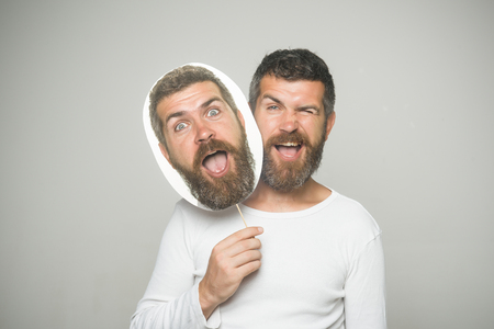 Feeling and emotions. Barber fashion and beauty. Hipster with winking and surprised face hold portrait nameplate. Man with long beard and mustache. Guy or bearded man on grey background.