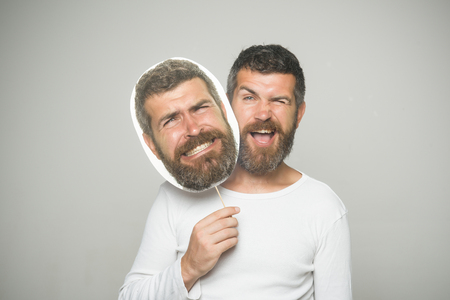 Guy or bearded man on grey background. Feeling and emotions. Man with long beard and mustache. Hipster with winking and scary face hold portrait nameplate. Barber fashion and beauty.